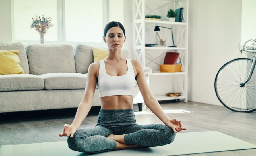 Women meditating in the living room of her home