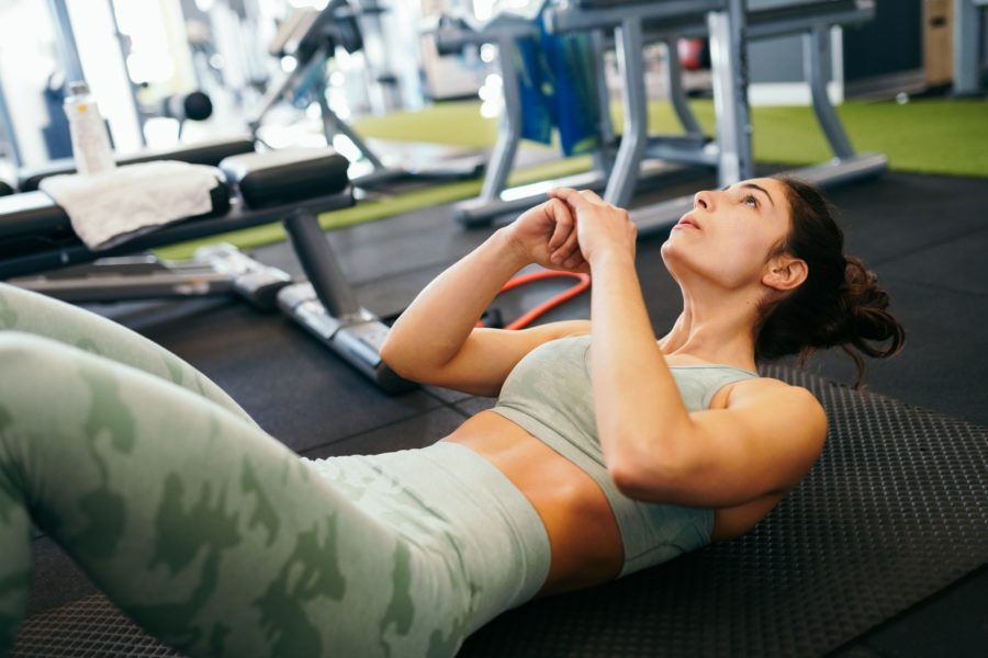 Young sportswoman on yoga mat doing sit-ups in gym